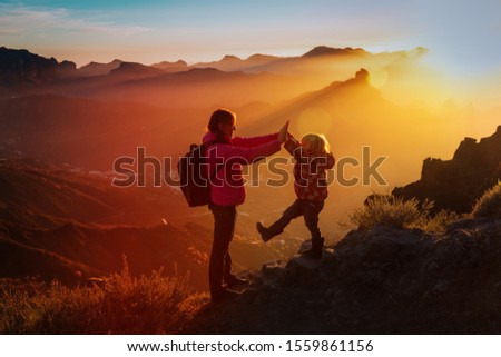 mother with little daughter enjoy travel in sunset mountains #1559861156