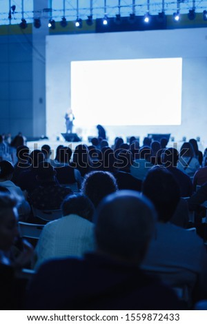 Audience listens to the lecturer at the conference hall. blue tinted photo Focus on unrecognizable people #1559872433