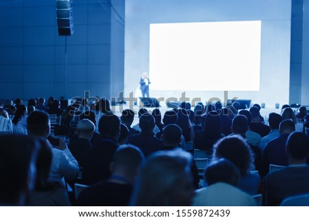 Business and Entrepreneurship concept. Speaker giving a talk in conference hall at business event. Audience at the conference hall. Focus on unrecognizable people #1559872439