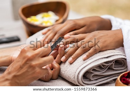 Close up of african woman hand getting manicure in spa salon. Detail of black hands getting manicure treatment at luxury spa. Girl in a nail salon receiving treatment by a beautician with nail-file. #1559873366