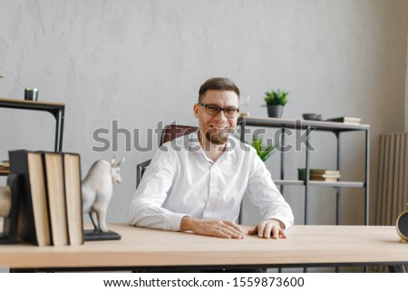 Portrait of young man sitting at his desk in the office and smiling at camera while sitting at workplace #1559873600