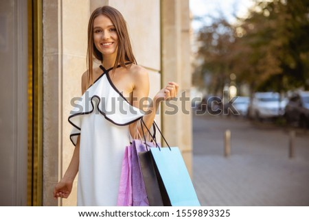 Good-looking young woman smiling at the porch of a shop #1559893325