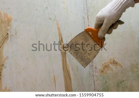 Preparing the wall for painting or sticking new wallpaper. Man in gloves with a scraper in the process of removing old wallpaper. wetted with a special solution surface #1559904755