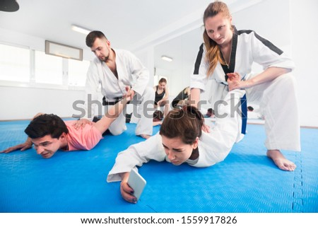 Young adults taking a photos while practicing a new taekwondo holds  #1559917826