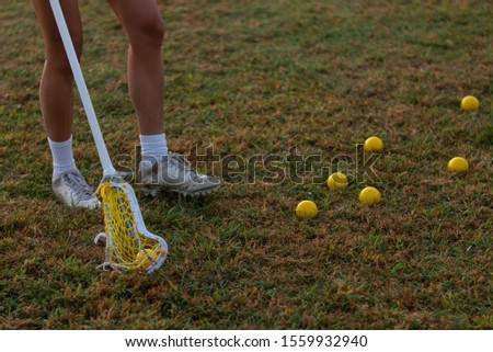 Female lacrosse player holding a women's lacrosse stick on a field.