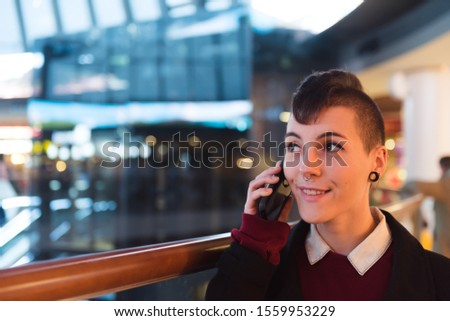 Female businesswoman with curly hair and modern style answers a call in a mall. #1559953229