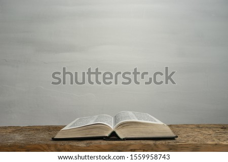 Open Holy Bible on a old wooden table and white wall background. Religion concept.