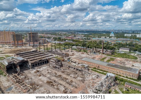Demolition work of a large old factory. Dismantling on the territory of a big city. Shooting from a great height, a large area. Sunny summer day. Royalty-Free Stock Photo #1559984711