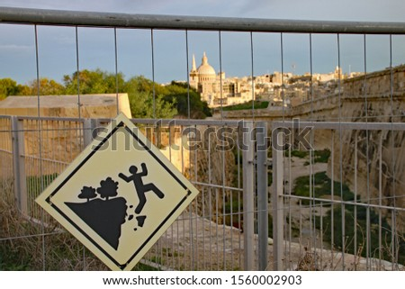 Sign attached to metal fence at Fort Manoel in Malta warning of the dangers of falling. The dome of St Paul's church in Valletta can be seen in the background #1560002903