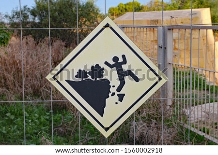 Sign attached to metal fence at Fort Manoel in Malta warning of the dangers of falling. #1560002918
