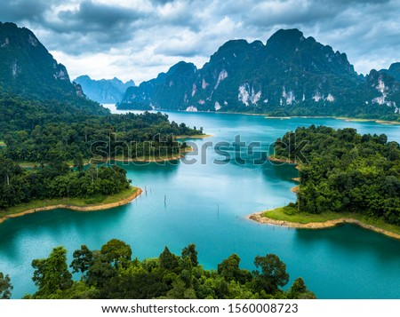Isolated island or tree in lake, Aerial photos from drones on beautiful lake in mountain at Ratchaprapha Dam and Cheow Lan Lake, Khao Sok, Thailand.