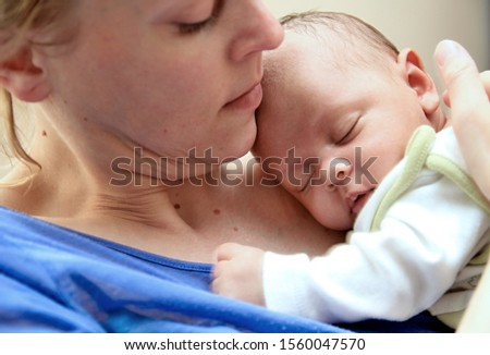 baby wrapped up in blanket with mother looking and just been cared for after having a good sleep in bed at home with people stock photography stock photo