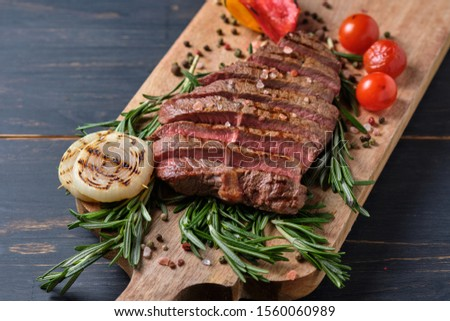Sliced freshly cooked steak with blood, served with grilled vegetables and fresh rosemary on a wooden board. Close-up. #1560060989