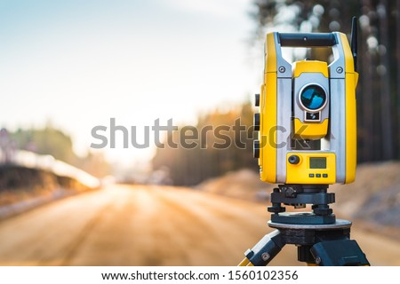 Surveyors equipment (theodolite or total positioning station) on the construction site of the road or building with construction machinery background Royalty-Free Stock Photo #1560102356