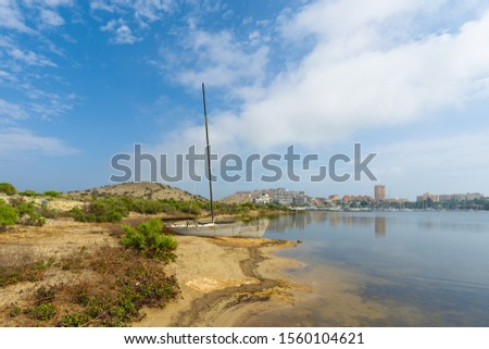 A white catamaran stands in the bay of Deer Island on the background of Port on La Manga del Mar Menor on a sunny day. Murcia, Spain
