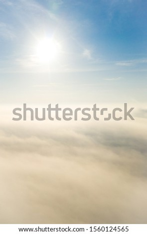Aerial photo above the fog or white clouds with shining sun. Beautiful sunrise cloudy sky from aerial view. Above clouds from airplane window or drone. #1560124565