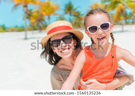 Little daughter and young mother at tropical beach. Family vacation #1560135236