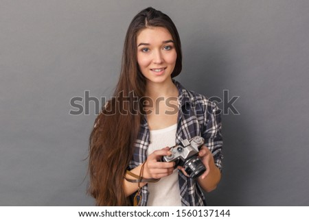 Young woman photographer standing studio isolated on grey background holding film camera looking camera smiling curious #1560137144