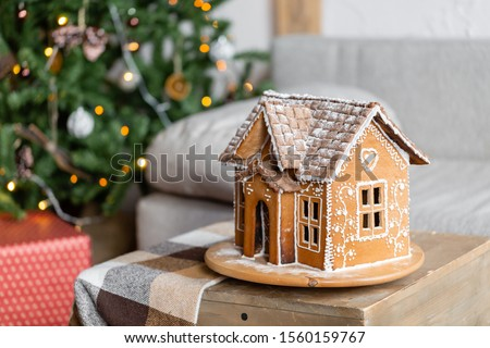 Gingerbread house, concept holiday of Christmas and Happy new year. Defocused lights of Christmas tree. Morning in the bright living room. Holiday mood. #1560159767