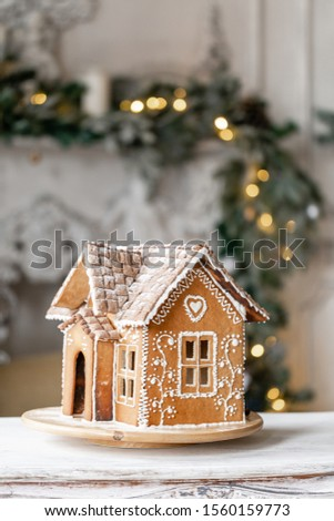 Gingerbread house, concept holiday of Christmas and Happy new year. Defocused lights of Christmas tree. Morning in the bright living room. Holiday mood. #1560159773