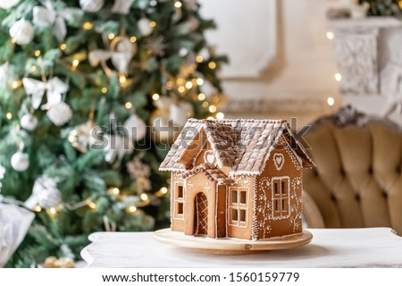 Gingerbread house, concept holiday of Christmas and Happy new year. Defocused lights of Christmas tree. Morning in the bright living room. Holiday mood. #1560159779