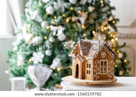 Gingerbread house, concept holiday of Christmas and Happy new year. Defocused lights of Christmas tree. Morning in the bright living room. Holiday mood. #1560159782