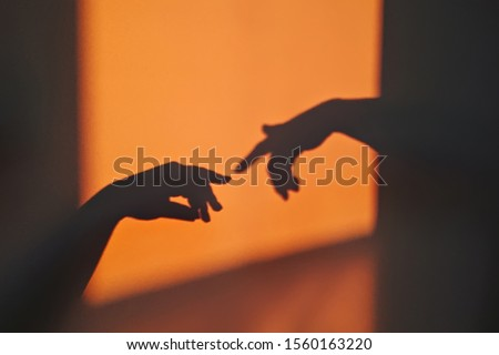 Abstract shadow silhouette of gesture touch by humans palms from sunbeam on wall during posing wrist and fingers. Creation of Adam metaphor by Michelangelo Royalty-Free Stock Photo #1560163220