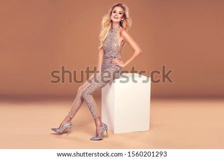 Beautiful young blonde woman in sexy glitter costume. Party carnival glamour photo #1560201293