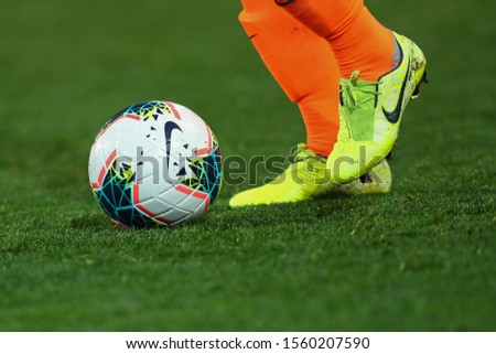 NOVEMBER 10 - KHARKIV, UKRAINE: Nike Merlin 2020 FIFA SOCCER BALL on a grass. Nike football boots. Close-up detailed view. Beautiful green pitch on the background. #1560207590