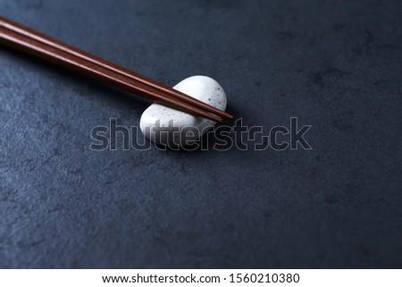 Wooden chopsticks and chopstick rest on dark stone background. Close up. Copy space.  #1560210380