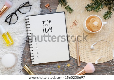 Flat lay of a blank spiral notebook with 2020 plans and goals mockup and Christmas decoration on a wooden and wool cozy background. Winter mood female home desk with fir branches. Copy space #1560235697