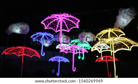 colorful umbrella from a small lamp at the night. Lighting the shape of an umbrella from a small lamp at a lamp festival in Indonesia.  #1560269969
