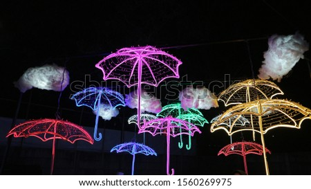 colorful umbrella from a small lamp at the night. Lighting the shape of an umbrella from a small lamp at a lamp festival in Indonesia.  #1560269975