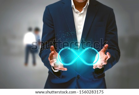 DevOps concept, an IT engineer holding the glowing devops symbol that illustrates the software development practices that combine development and operation teams and automates software processes  #1560283175