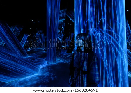 Shanghai/China-Oct.2019: In teamLab Borderless Shanghai art gallery. One girl in falling water projections. Dark background #1560284591