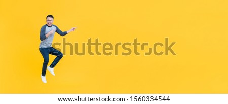 Casual smiling Asian man jumping and pointing fingers to copy space aside isolatede on yellow banner background #1560334544