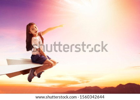 happy little  girl on paper plane and  flying in the sky #1560342644