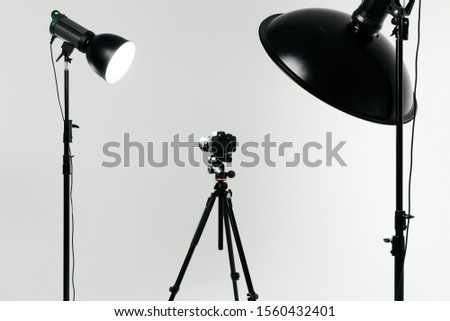 Photo camera with macro lens on the tripod side view. Studio shot. Studio light equipment #1560432401