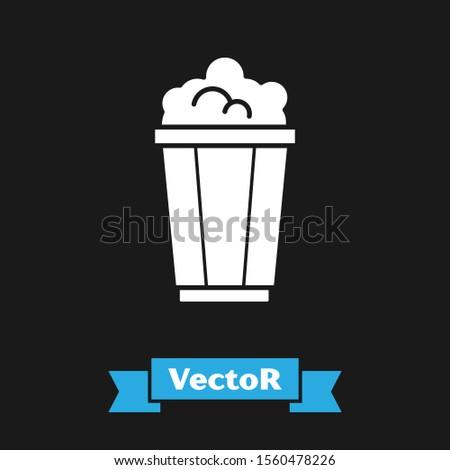 White Popcorn in cardboard box icon isolated on black background. Popcorn bucket box.  Vector Illustration #1560478226
