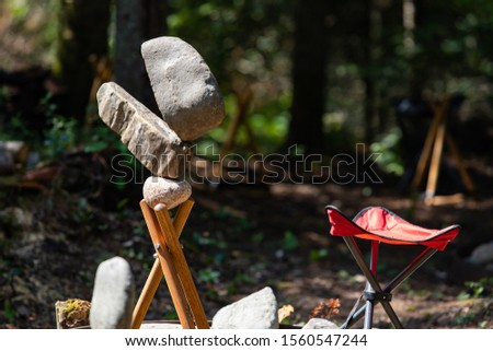 Rock balancing or stone balancing, selective focus of Balanced Stones and Small chair in the forest #1560547244