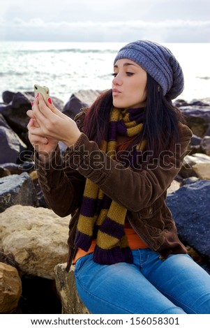 Young woman with scarf and hat taking picture of herself with iphone