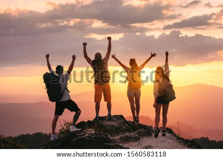 Happy friends hikers or tourists stands with raised arms on mountain top against mountains and looking at sunset #1560583118