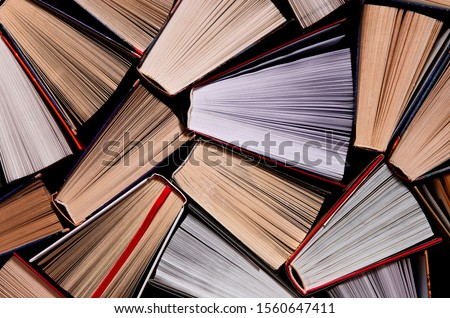 Books. Lots of colourful thick open books stand on a dark background #1560647411