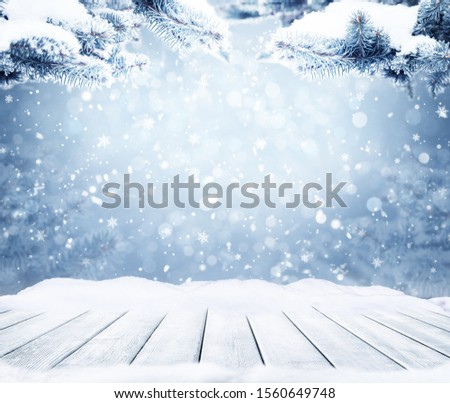 Winter Christmas background with bokeh lights, snowflakes and empty old wooden table. Christmas and Happy New Year background with snowflake. Winter landscape with falling snow and fir tree branches. #1560649748