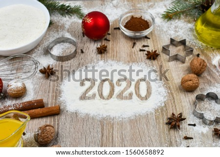Tools and products for baking homemade gingerbread cookies on a wooden background with the inscription 2020. The concept of the holiday, celebration and cooking.  #1560658892