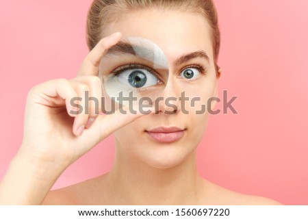Young woman looking at the camera through magnifier with funny surprised expression, closeup isolated on pink. Enlarged eye, optical illusion, search