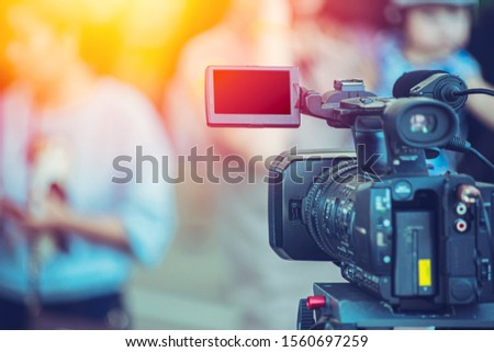 Video camera camcorder operator working at live event broadcasting blue color tone. #1560697259