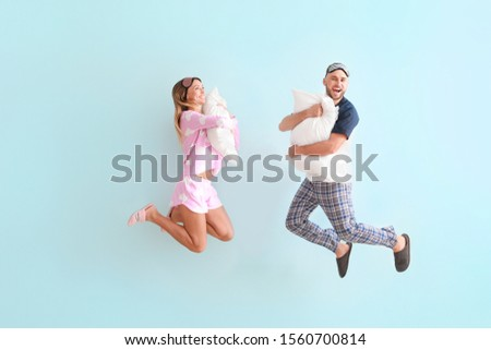 Jumping young couple with pillows on color background #1560700814
