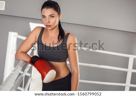 Young woman boxer wearing gloves standing leaning on rope on boxing ring looking camera smiling confident #1560799052