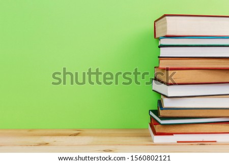 Simple Simple composition of many hardback books, unprocessed books on a wooden table and a green background. back to school. Copy space. Education. #1560802121